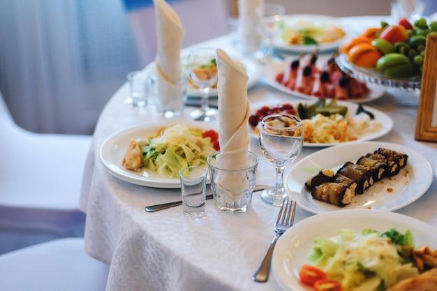 Tavolo festivo con tovaglie bianche, bicchieri per bevande e cibo nel ristorante al banchetto