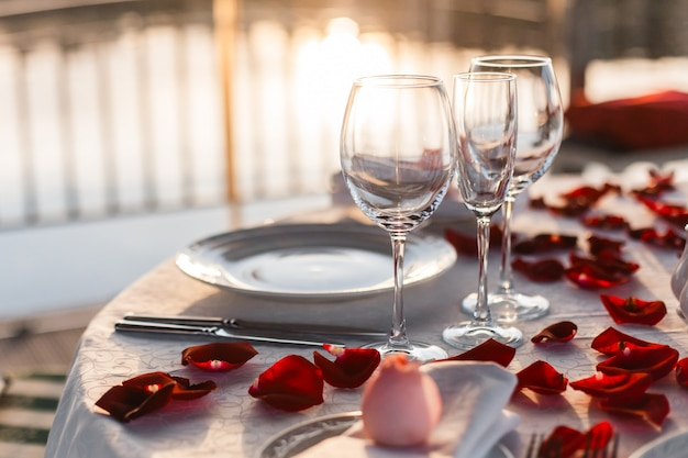 Tavolo festivo servito per una cena romantica per una coppia sulla terrazza sul mare