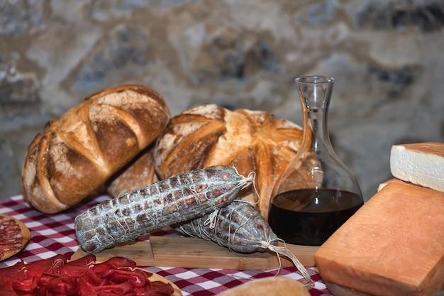 Tavolo in fattoria con salame pane vino e formaggi locali