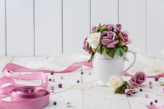 Tavolo in legno bianco con fiori rosa, nastri e perline. stile di nozze