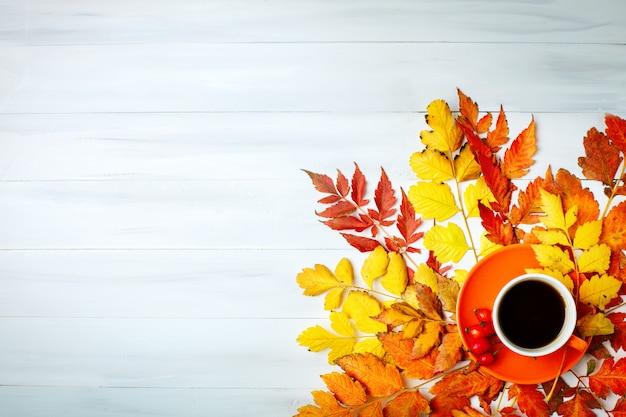 Tavolo in legno bianco decorato con foglie di autunno e una tazza di caffè. sfondo autunno con spazio di copia.