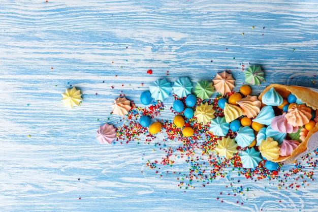 Tavolo in legno blu pieno di caramelle, lecca-lecca, biscotti e cibo dolce e malsano