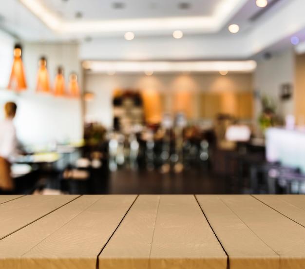 Tavolo in legno con scena ristorante offuscata
