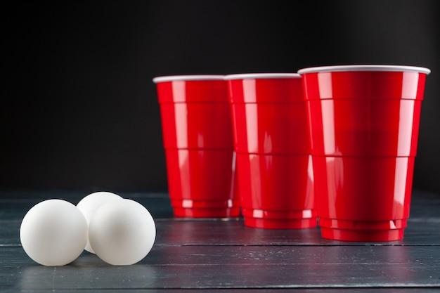 Tavolo in legno con tazze rosse e palla per birra pong