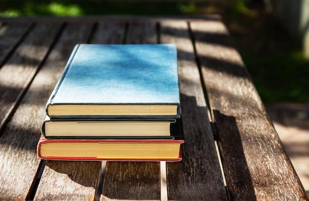 Tavolo in legno con tre libri uno sopra l'altro durante il giorno