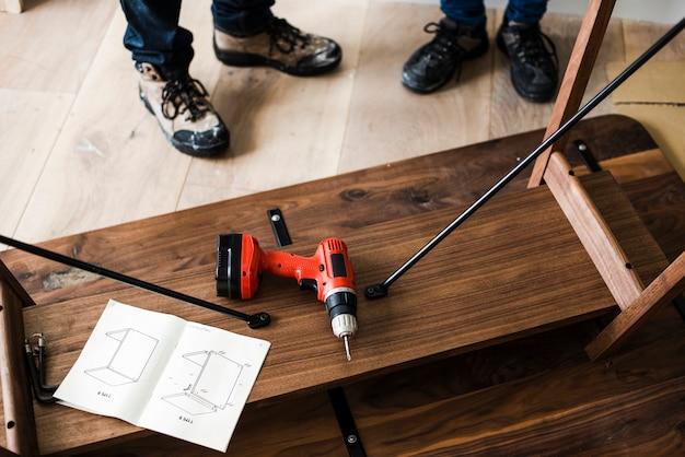 Tavolo in legno con un trapano a mano