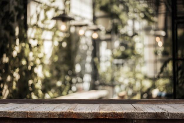 Tavolo in legno di fronte al giardino interno con tavolo e lampadina decorata