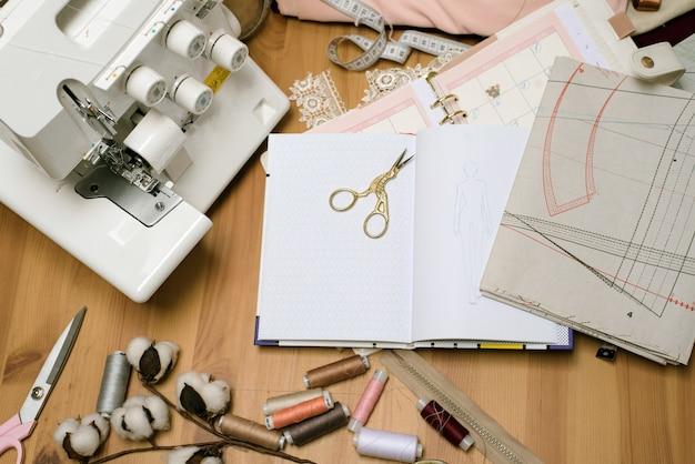 Tavolo in legno di sarta con forbici sparse, un overlock, una macchina da cucire, disegni, fili e bozze con tessuti. spazio con oggetti di lavoro sarta