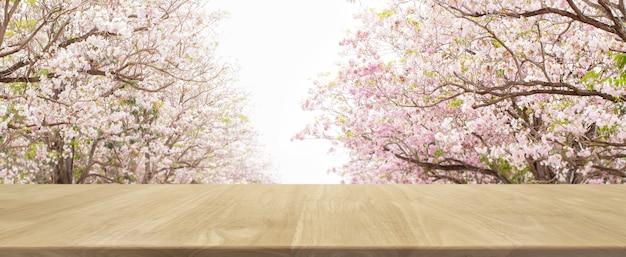 Tavolo in legno e albero di fiori sfocato sfondo parco banner - può essere utilizzato per la visualizzazione o il montaggio dei vostri prodotti.