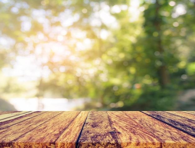 Tavolo in legno e immagine sfocatura dell'albero.