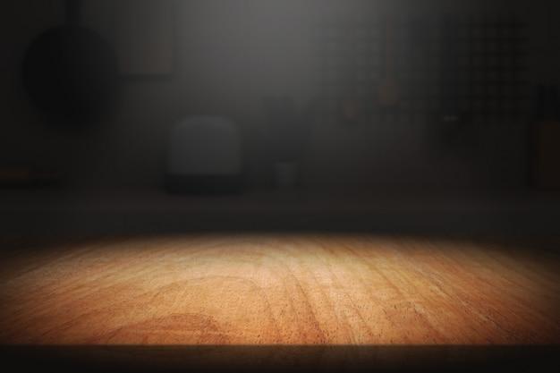 Tavolo in legno in camera oscura con sfondo chiaro.
