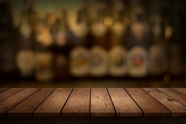 Tavolo in legno in vista di sfondo sfocato bottiglia di bevande bar.