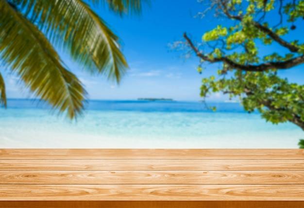 Tavolo in legno marrone sulla spiaggia tropicale di estate.