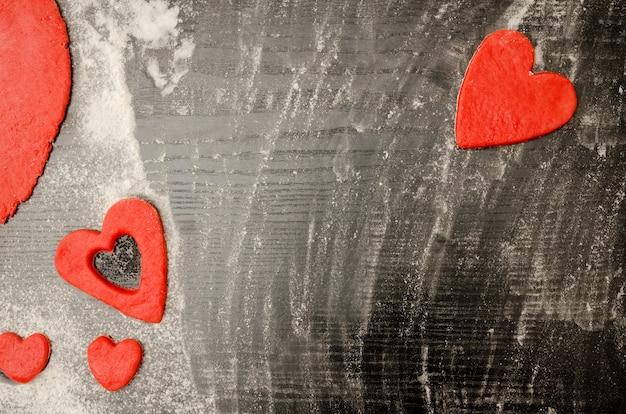 Tavolo in legno nero con farina, cuore rosso fatto di pasta attorno ai bordi della cornice. vista dall'alto, spazio per il testo