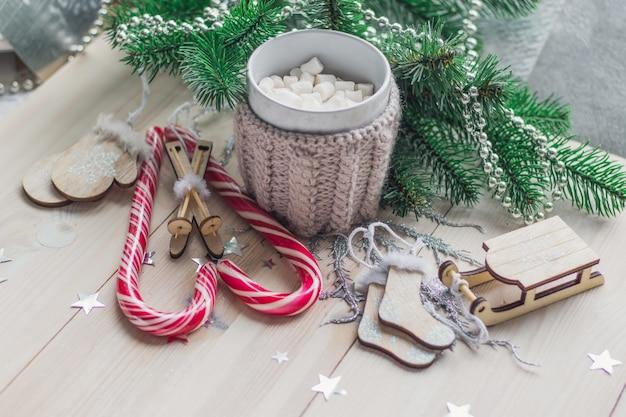 Tavolo in legno ricoperto di caramelle gommose marshmallow e decorazioni natalizie sotto le luci