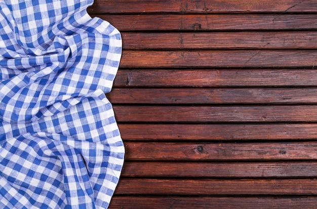 Tavolo in legno scuro con tovaglia a quadretti blu, vista dall'alto con spazio di copia