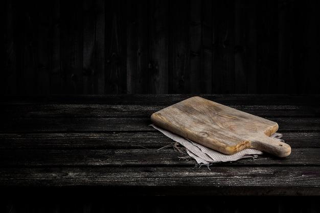 Tavolo in legno scuro per prodotto, vecchio interno prospettiva in legno nero con tagliere vecchio