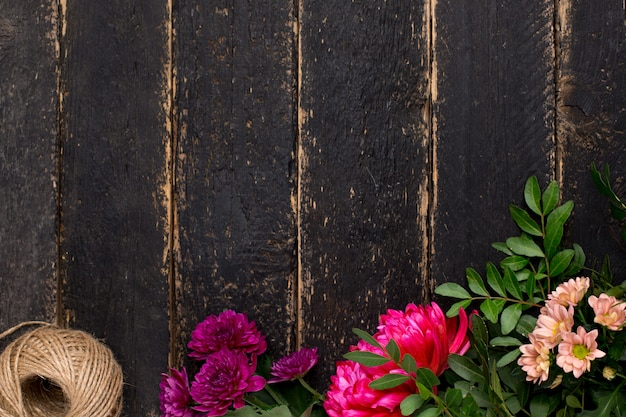 Tavolo in legno scuro vintage con fiori e spago