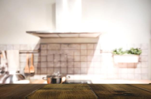Tavolo in legno su sfocatura interno del fondo della cucina