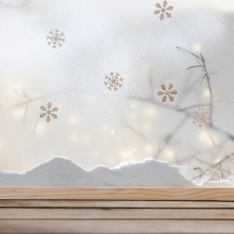 Tavolo in legno vicino banca di neve, fiocchi di neve e luci fiabesche