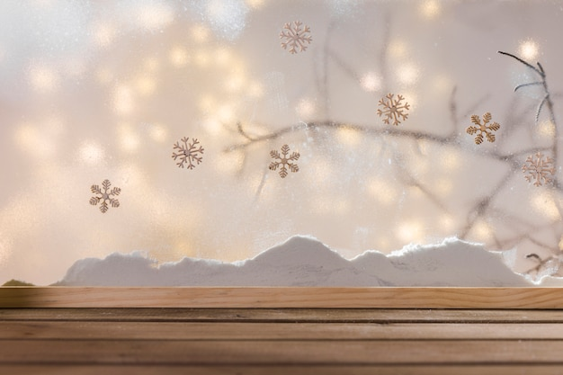 Tavolo in legno vicino banca di neve, ramoscello di piante, fiocchi di neve e luci fiabesche