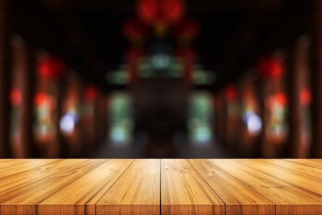 Tavolo in legno vuoto con sfondo sfocato caffetteria o ristorante interno.