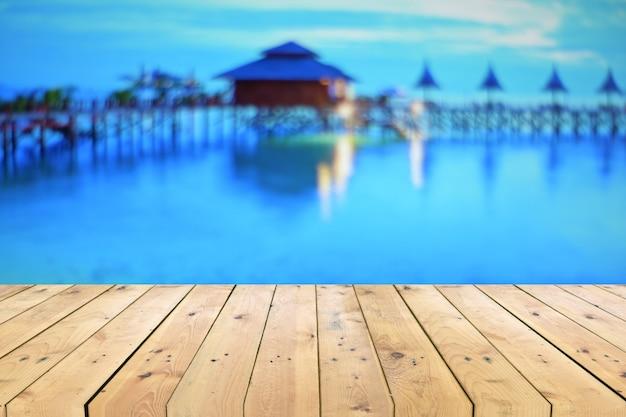 Tavolo in legno vuoto con vista sul mare offuscata