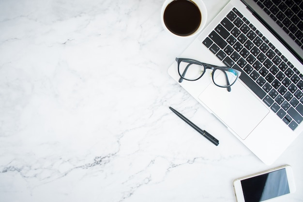 Tavolo in marmo con laptop, smartphone, bicchieri e caffè nella vista dall'alto con spazio di copia, piatto lay.