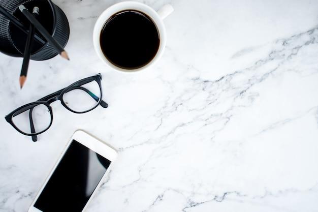 Tavolo in marmo con smartphone, bicchieri e caffè nella vista dall'alto. affari moderni.