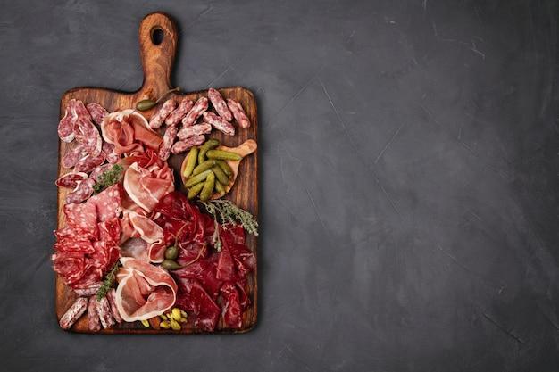 Tavolo per antipasti con diversi antipasti, formaggi, salumi, snack e vino. salsiccia, prosciutto, tapas, olive, formaggio e cracker per la festa a buffet.