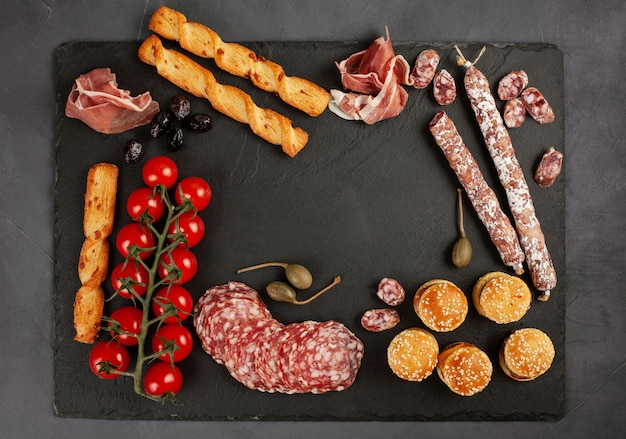Tavolo per antipasti con diversi antipasti, formaggi, salumi, snack e vino.