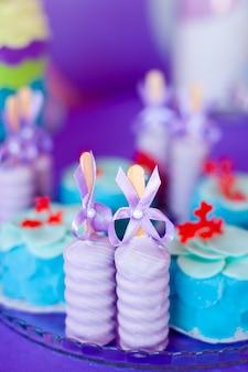 Tavolo per bambini con cupcakes con piano blu e rosso e oggetti decorativi