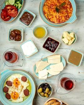 Tavolo per la colazione con diversi tipi di uova fritte, formaggi, miele, cioccolatini e tè