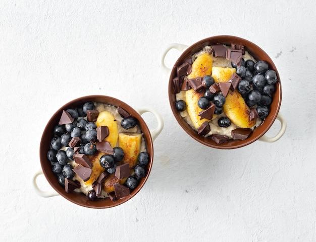 Tavolo per la colazione con farina d'avena piastra con banana fritta, cioccolato e mirtillo su una vista superiore bianca