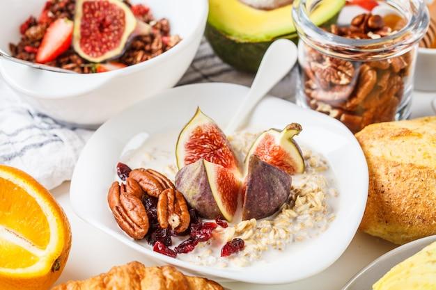 Tavolo per la colazione con toast di avocado, farina d'avena, waffle, cornetti su sfondo bianco.