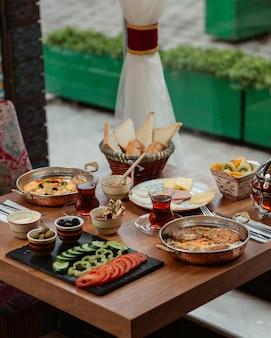 Tavolo per la colazione con una varietà di cibi, formaggi, verdure, omelette, salsicce, miele e olive.