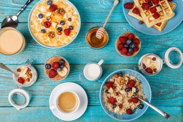Tavolo per la colazione con waffle, farina d'avena, cereali, caffè, succo di frutta e bacche fresche