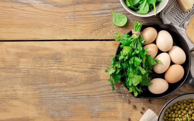 Tavolo per la colazione sano con ingrediente per cucinare. piselli, uova, spinaci, prezzemolo e formaggio su fondo in legno copyspace vista dall'alto