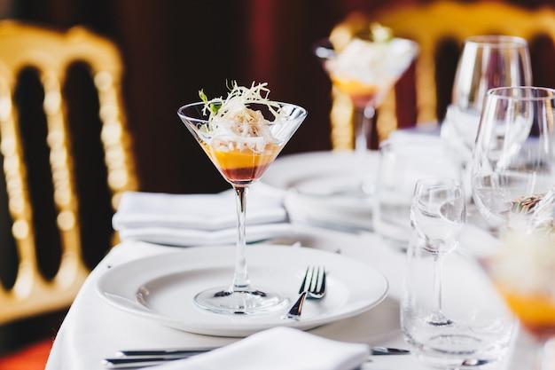 Tavolo per matrimoni decorato con piatti bianchi, bicchieri per vino e cocktail nell'ampia sala