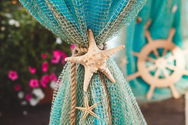 Tavolo per pittura cerimonia sul posto in stile marino. decorato con reti, conchiglie, ancora e timone