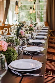 Tavolo per ricevimento di nozze con lampadine edison e decori di verde.