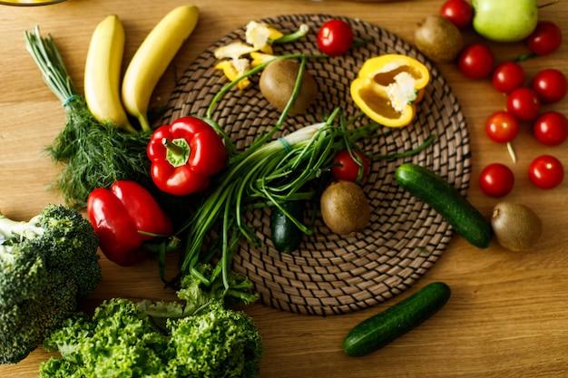 Tavolo piatto con frutta e verdura fresca, peperoni, cipolla, cetrioli, pomodori, vibrazioni sane