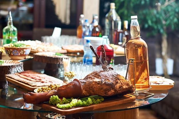 Tavolo pieno di cibi e bevande alcoliche al ristorante. carne di maiale affumicata servita su un piatto di legno.