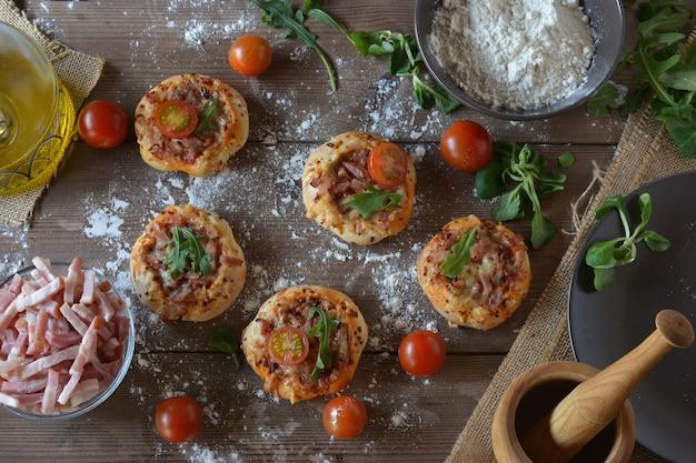 Tavolo rustico con mini pizze di speck