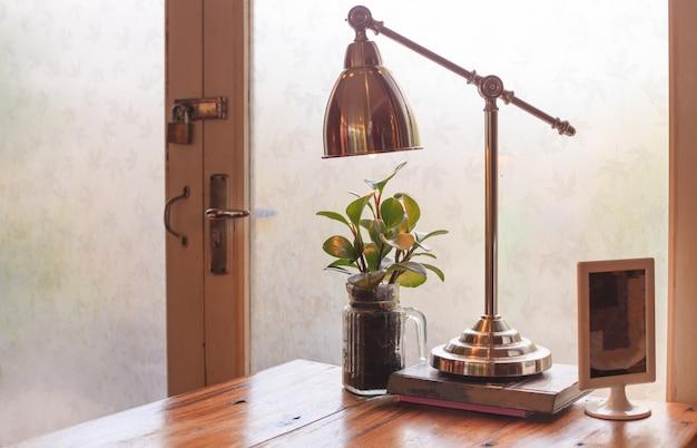 Tavolo rustico in legno da lettura con calda luce naturale, illuminato da una porta finestra in vetro.