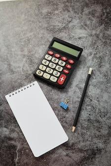 Tavolo scrivania con calcolatrice con taccuino vuoto