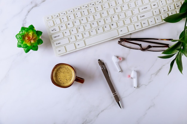Tavolo scrivania con computer forniture cuffie occhiali penna e tazza di caffè