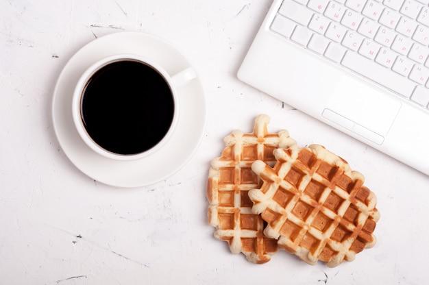 Tavolo scrivania con computer portatile, tazza di caffè e cialde su sfondo chiaro
