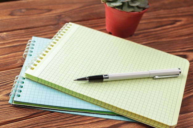 Tavolo scrivania da tavolo. blocco note con pagine bianche sul tavolo di legno