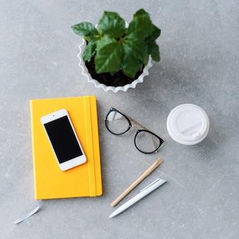 Tavolo scrivania da ufficio con agenda notebook, smart phone, bicchieri e tazza di caffè.